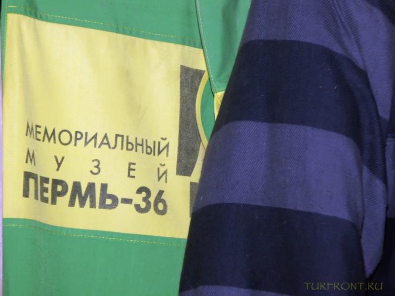 Зона-музей Пермь-36: Рукав робы зэка на фоне тряпичного транспаранта с названием зоны. (фотография №1)