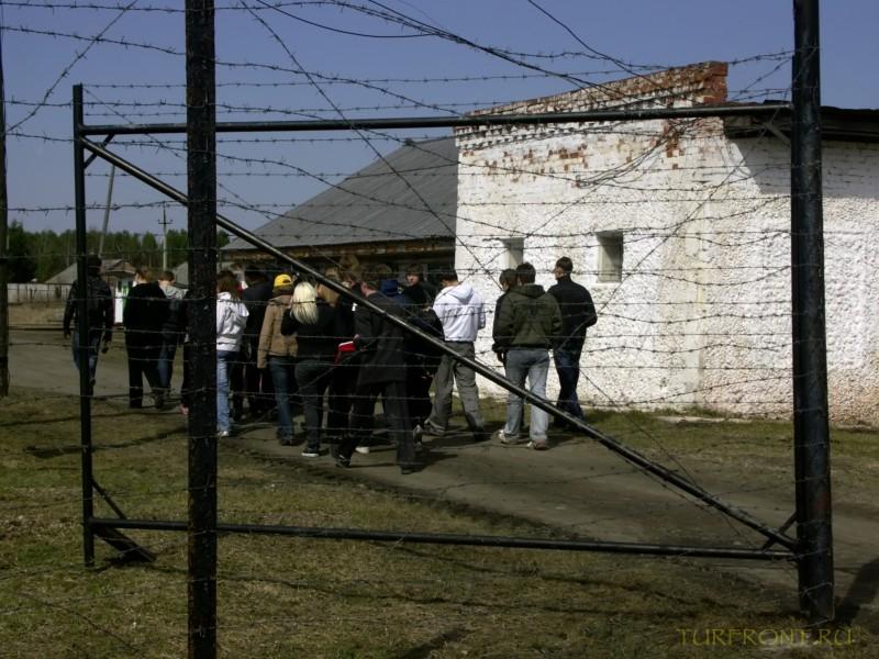 Зона-музей Пермь-36: Группа посетителей зоны за колючками ворот. (фотография №4)