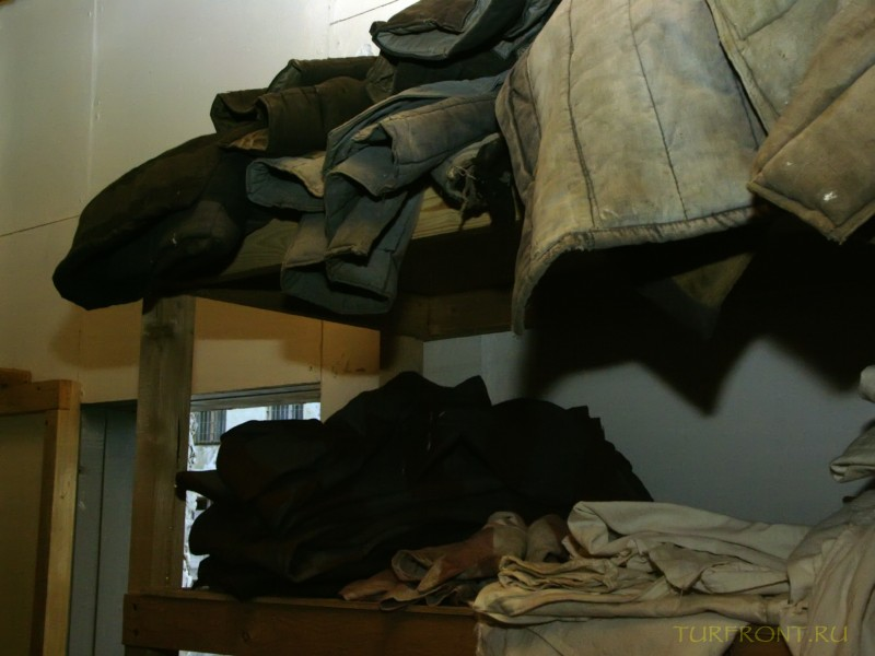 Зона-музей Пермь-36: Зековские ватники, сложенные на полке. (фотография №42)