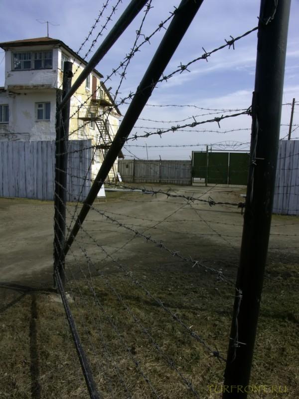 Зона-музей Пермь-36: Забор с колючей проволокой и здание администрации зоны вдалеке. (фотография №51)
