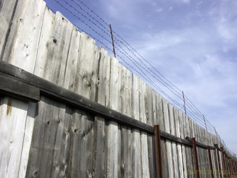 Зона-музей Пермь-36: Забор с колючкой на фоне неба с облаками. (фотография №61)