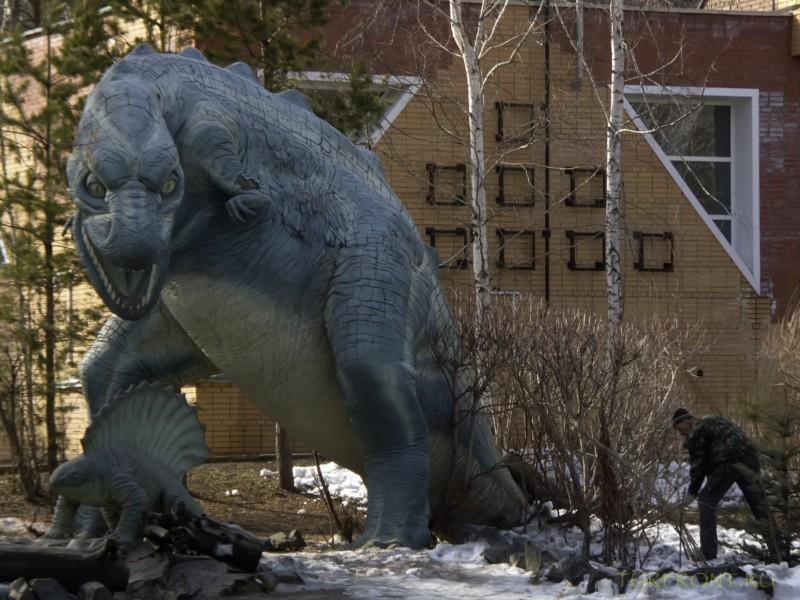 Новосибирский зоопарк: Рабочий с лопатой около каменного динозавра. (фотография №5)