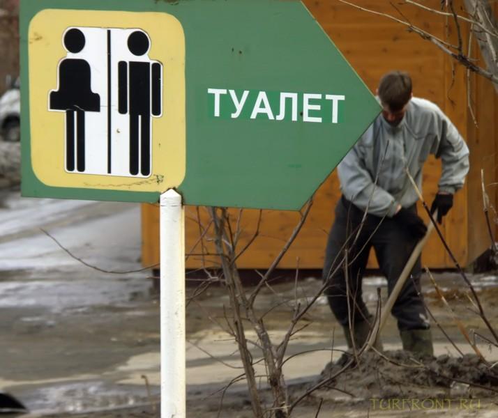 Новосибирский зоопарк: Рабочий, копающий яму рядом с указателем на туалет. (фотография №30)