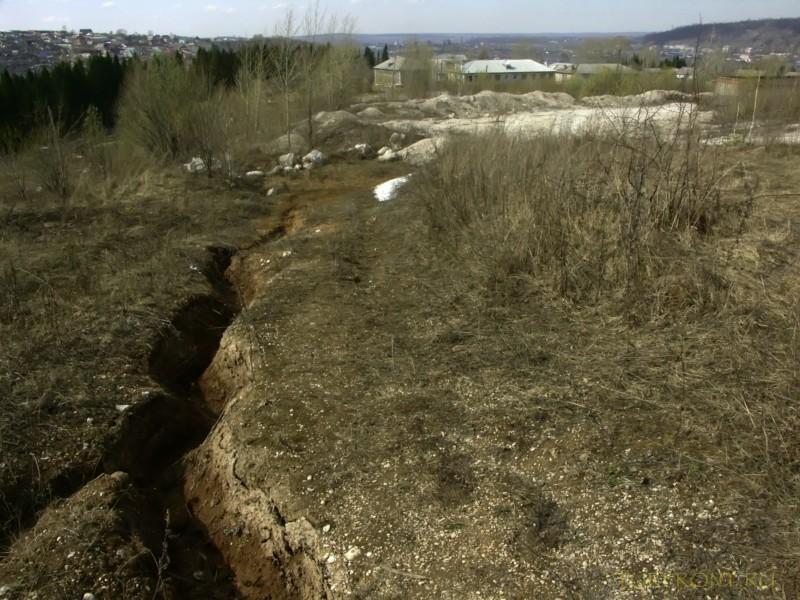 Каменный карьер города Чусовой: Трещина в земле и панорама домов Чусового вдали.   (фотография №4)