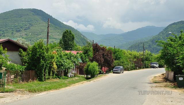 Улица поселка Цандрипш в Абхазии на фоне гор и голубого неба.   Фото 1